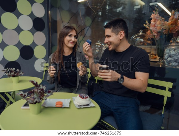 couple having fun in a cafe, drink coffee and eat desert