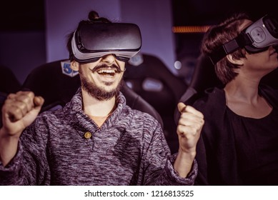 a couple having fun in a cinema wearing virtual glasses with special effects