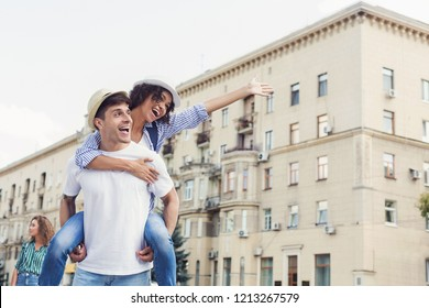 Couple having fun. Man giving piggyback ride to woman in city, copy space
