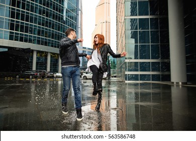 Couple having fun near puddle of rain. Wet shoes and raindrops