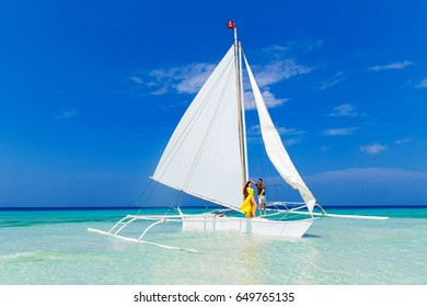 Couple having fun on tropical beach on the sailboat. Summer vacation concept.