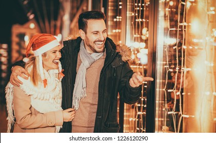 Couple having fun outdoors at Christmas time pointing at something behind shop window.