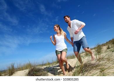 Couple having fun runnning down sand dune