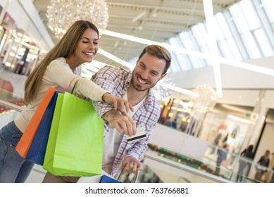 Couple having fun in shopping mall while doing shopping together