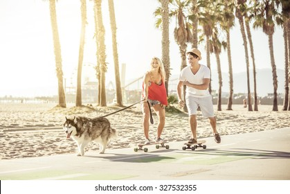 Couple having fun with their Husky dog. the animal pulling while the woman is on the skateboard