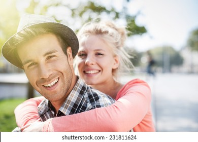 Couple having fun in town, the young woman on the boy's shoulders