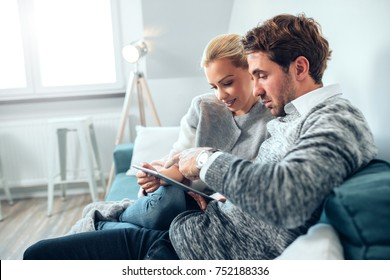 Couple having fun using digital tablet at home.