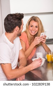Couple having fun using smartphone at breakfast time