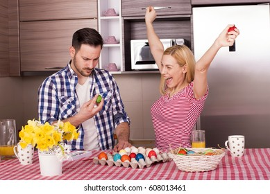 Couple Having Fun while Cracking Colored Easter Eggs