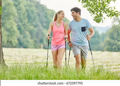 Couple having fun while nordic walking in the park