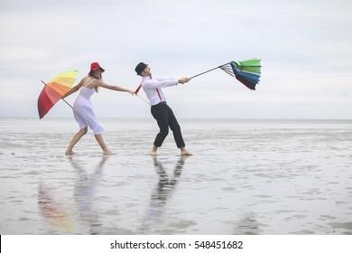 Couple having fun at a windy beach with broken umbrella