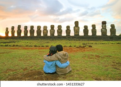 Couple having a happy moment in front of the awesome Moai statues of Ahu Tongariki at sunrise, Archaeological site in Easter Island, Chile