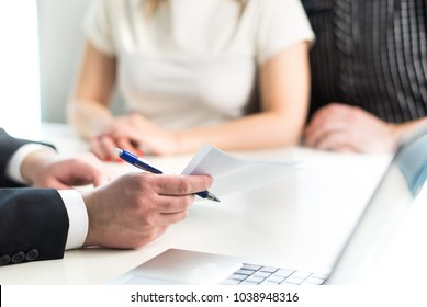 Couple having meeting with legal advisor, real estate agent, businessman or banker. Lawyer giving advice or consultant showing document or agreement to man and woman. Insurance or car leasing paper.