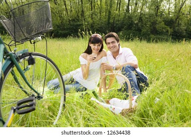 couple having a picnic in a park, smiling and looking at the camera