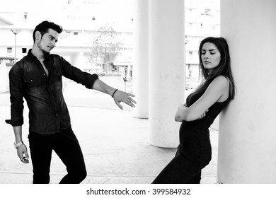 Couple having problem. Woman with crossed arms looking down. Ma pulling arm towards her. Black and white.