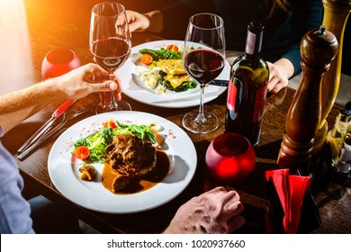 Couple having romantic dinner in a restaurant in rays of the sun