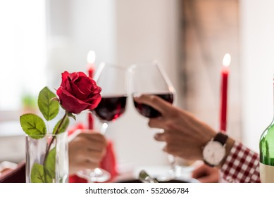 couple having a romantic dinner and toasting with cups of red wine.