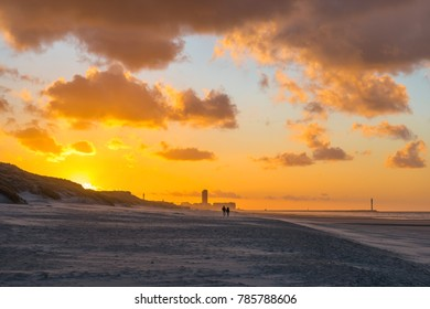A couple having a romantic walk on the North Sea beach of Ostend at sunset with its skyline in the background, West Flanders, Belgium.