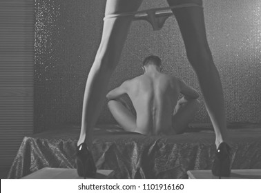 Couple having sex. Back view of woman in black panties holding her bra while man is lying on bed. Strong male. Sensual. Adult. Sexy man and woman. Erotic game. Shadow. Black and white photo. Energy.