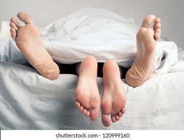 Couple having sex in bed under sheets.