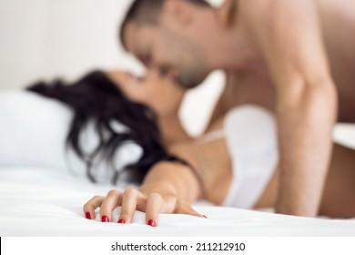 Couple having sex, female hand grabbing sheet