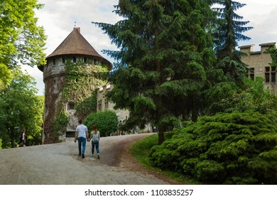 Couple heading for entrance gate into medieval Smolenice castle (SLOVAKIA)