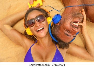 Couple  with headphones sunbathing in summertime