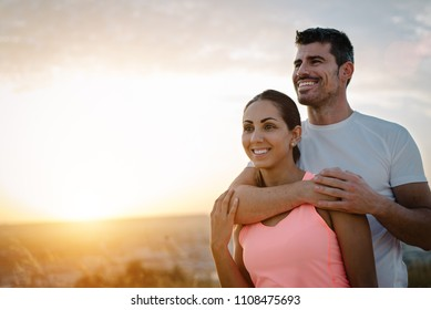 Couple healthy and fitness lifestyle. Happy sporty lovers portrait during outdoor training at sunset.