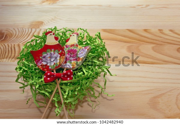 couple of hens painted with flowers lying in nest on wooden background