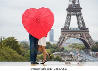 The couple hidden with red umbrella in front of the Eiffel tower in Paris