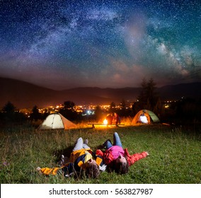 Couple of hikers enjoying the bright stars and lying on the grass in the background night tent camping with their friends near campfire, mighty mountains, luminous town