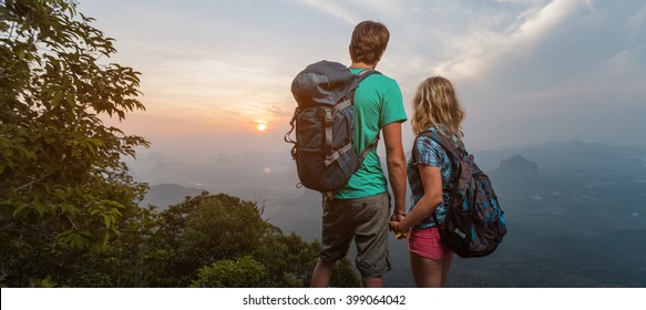 Couple of hikers enjoying sunrise on top of the mountain