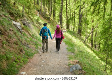 A couple hikers Hiking with backpacks walk along a beautiful mountain area holding hands . The concept of active rest. Switzerland 2017