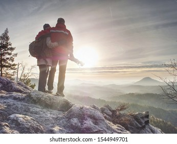 Couple of hikers look down into fogy valley. Photographer stay on cliff and takes photos. Dreamy fogy landscape blue misty sunrise in a beautiful valley below