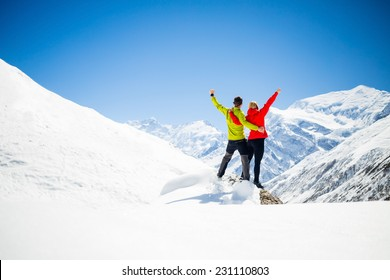 Couple hikers man and woman success in winter mountains. Inspiration and motivation in beautiful landscape. Fitness healthy lifestyle outdoors on snow in Himalayas, Nepal. Annapurna range trekking sky