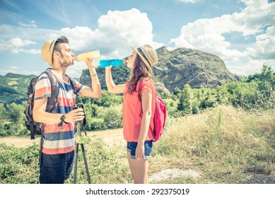 Couple of hikers on an excursion in the nature - Tourists having a pause while on a trekking tour - Two young sportive tourists having a walk in the countryside