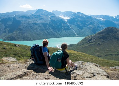 couple of hikers resting and looking at Besseggen ridge over Gjende lake in Jotunheimen National Park, Norway