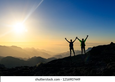 Couple hikers success and trust in mountains, accomplish with arms up outstretched. Young man and woman looking at beautiful inspirational landscape view, Gran Canaria Canary Islands.