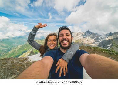 Couple of hikers taking selfie from top of the mountain with peaks and valley view on the background