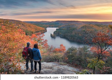 a couple of hikers taking in the spectacular autumn view at sunset