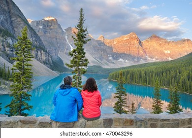 a couple of hikers welcome the start of the day at Moraine lake