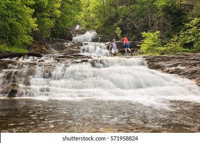 a couple hiking along a beautiful waterfall