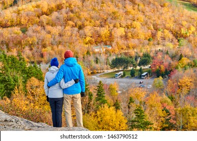 Couple hiking at Artist's Bluff in autumn. Fall colours in Franconia Notch State Park. White Mountain National Forest, New Hampshire, USA