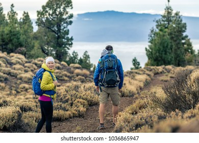 Couple hiking with baby boy travelling in backpack. Hikers family, adventure with child on autumn family trip in mountains. Vacations with infant carried on back, weekend travel in Tenerife, Spain.