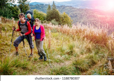 Couple hiking with baby boy travelling in backpack. Hikers family, adventure with child on autumn family trip in mountains. Vacations journey with toddler carried on back, weekend travel concept.
