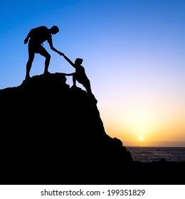 Couple hiking help each other hand teamwork partners climbing silhouette in mountains, achieve adventure. Male and woman hiker helping each other on top of mountain, beautiful sunset landscape.