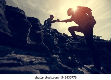 Couple hiking help each other silhouette in mountains with sunlight
