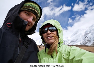 Couple hiking in Himalaya Mountains in Nepal. Man and woman taking self-portrait on trekking on mountain glacier. Young people traveling in Asia, trekkers on trail in wilderness.