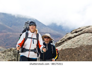 Couple hiking in himalayas mountains in Nepal. Young people traveling in Asia, man and woman trekkers on trail in wilderness.
