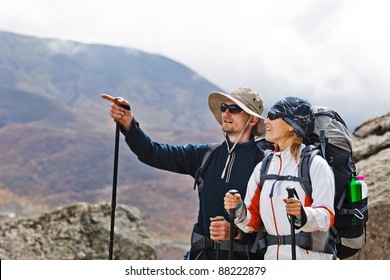 Couple hiking in himalayas mountains in Nepal. Young people traveling in Asia, trekkers on trail in wilderness.